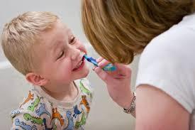 mum brushing child's teeth