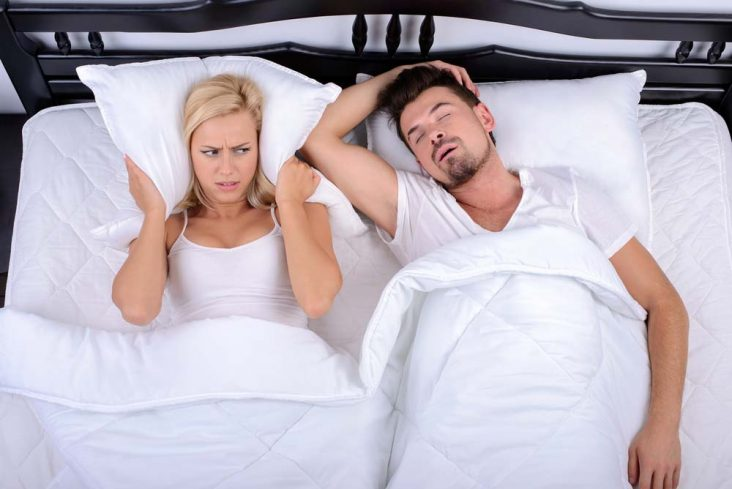 Young woman struggles to get to sleep through man's snoring