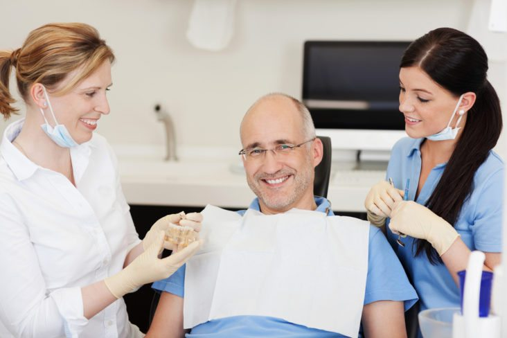 A dentist and dental assistant explaining dental implants to a patient